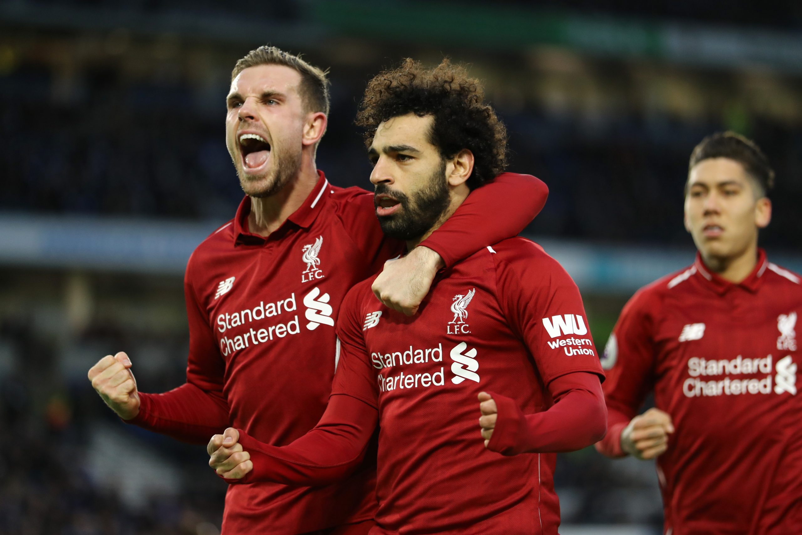 Mohamed Salah of Liverpool celebrates with team mate Jordan Henderson after scoring their first goal from the penalty spot against Brighton and Hove Albion in the January 2019 league fixture. (GETTY Images)